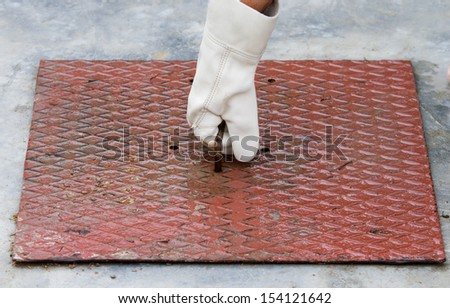 man lifts the manhole cover - stock photo