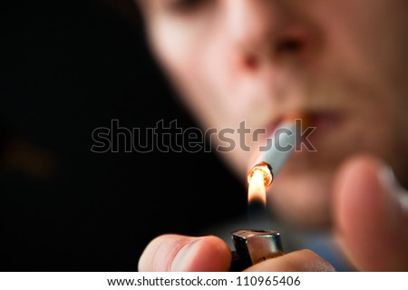 Man lighting a cigarette against a black background - stock photo