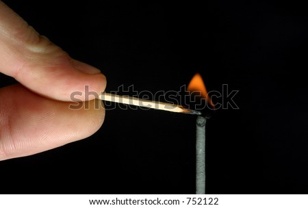 Man lighting a fuse with a safety match - stock photo