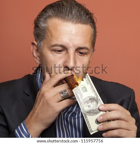 Man lighting his cigar with 100 dollars banknote