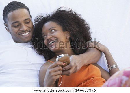 Man listening to mp3 player hugging girlfriend - stock photo