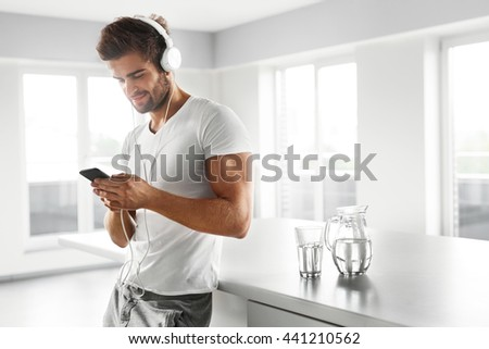 Man Listening To Music In Fashion Headphones Using Mobile Phone, Smartphone Indoors. Portrait Of Handsome Happy Relaxed Smiling Guy  Enjoying Music At Home. Entertainment, Communication Concept - stock photo
