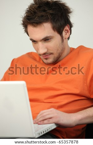 Man listening to music in front of a laptop computer - stock photo