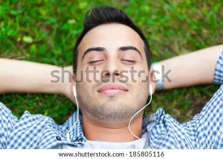 Man listening to music laying on the grass - stock photo