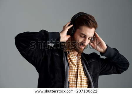 Man listening to music relaxing and enjoying good sound quality on professional dj headphones - stock photo