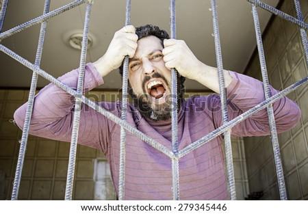 Man locked bars, aggressive and furious - stock photo