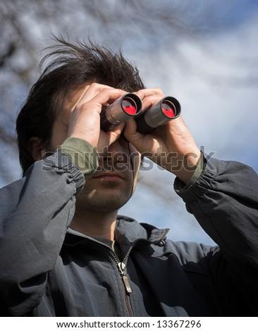 Man look through the  binoculars - stock photo