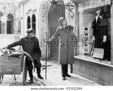 Man looking at a window display of a tuxedo - stock photo