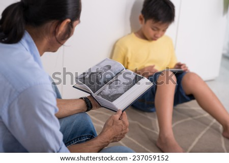 Man looking at baby photos of his son in the photo album, while the boy playing on tablet - stock photo