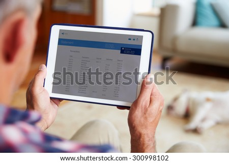 Man Looking At Banking App On Digital Tablet