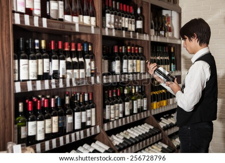 man looking at bottle of wine in supermarket. - stock photo
