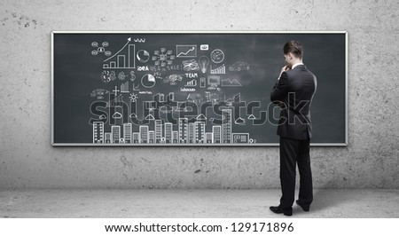 man looking at business strategy on blackboard