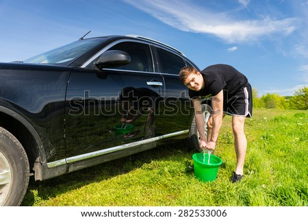 Man Looking at Camera and Wringing Out Soapy Sponge into Green Bucket While Washing Black Luxury Vehicle in Green Grassy Field on Bright Sunny Day with Blue Sky