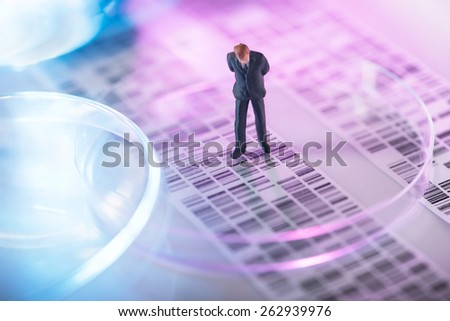 Man looking at DNA gel into petri dish - stock photo