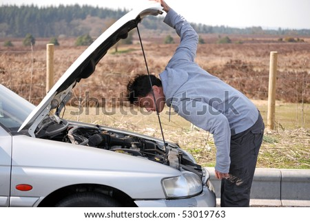 Man looking at engine of car - stock photo