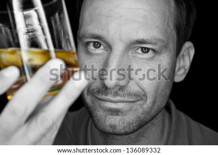 man looking at golden whiskey or brandy on the rocks, color-key - stock photo