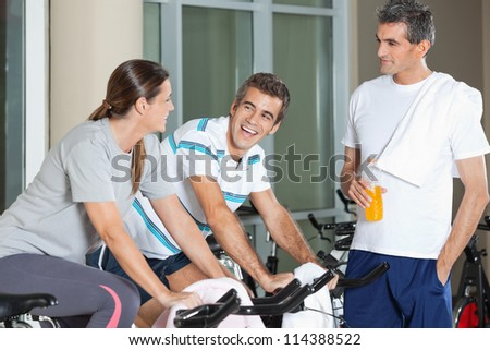 Man looking at happy friends exercising on spinning bike in health club - stock photo