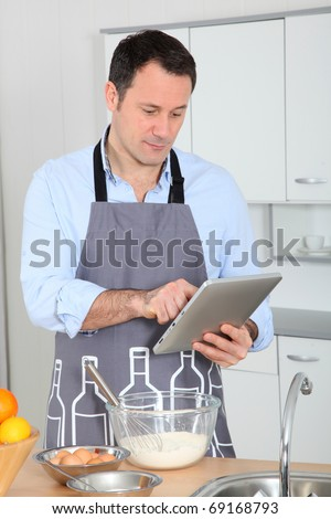 Man looking at recipe on internet - stock photo