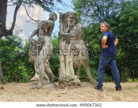 Man looking at Satyr and nymph statues, mythological symbols of sexuality