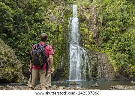 Man looking at scenic waterfall in New Zealand - stock photo