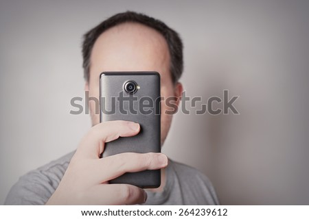 man looking at smart phone or taking selfie picture with camera mobile      - stock photo
