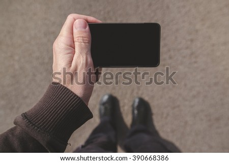 Man looking at smartphone screen while walking on street, top view pov perspective with blank mobile display as copy space, using mobile app for navigation outdoors. - stock photo