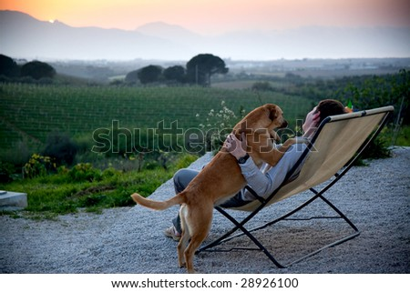man looking at sunset with his dog - stock photo