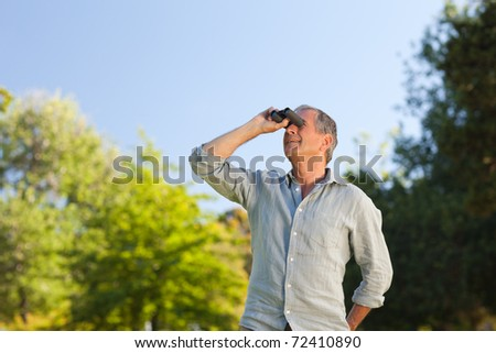 Man looking at the sky with his binoculars - stock photo