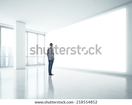 man looking at white wall in the office - stock photo