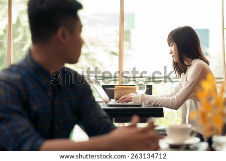Man looking at woman who is working on laptop in a cafe