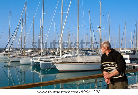man looking at yachts, marina, North Cyprus - stock photo