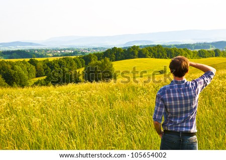 man looking far away standing on green filed