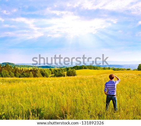Man looking far away standing on green filed - stock photo
