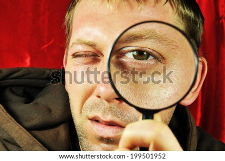 Man looking for something using magnifying glass - stock photo