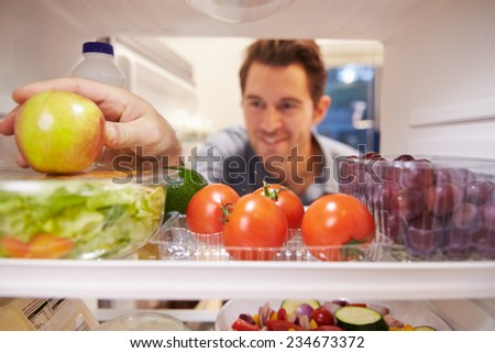 Man Looking Inside Fridge Full Of Food And Choosing Apple - stock photo