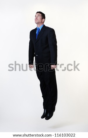 man looking like he is taking of into the air like a rocket - stock photo