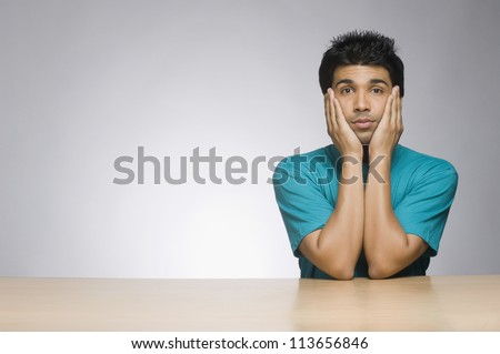 Man looking serious with his head in his hands