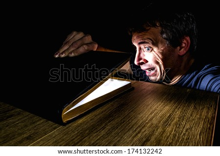 man looking shocked at the light coming out of a book - stock photo