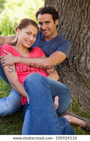 Man looking straight ahead as he holds his smiling friend while they sit together against the trunk of a tree