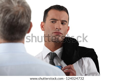 Man looking suspiciously at his colleague - stock photo