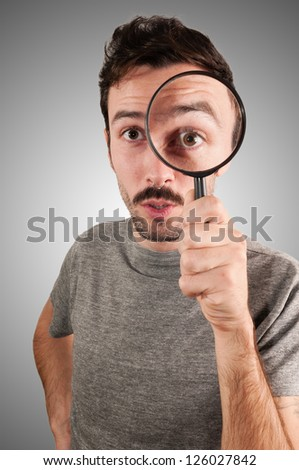 man looking through a magnifying lens on gray background