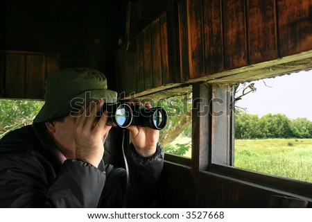 Man looking through binoculars in a birdwatching hideout - stock photo
