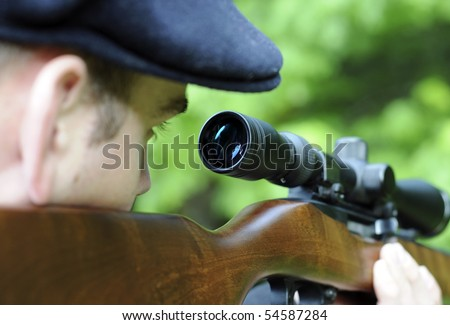 Man looking through the scope on his wooden rifle gun - stock photo