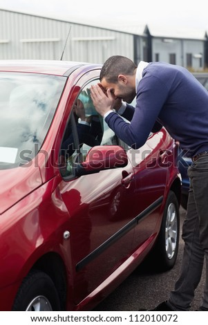 Man looking through the window of the car outdoors
