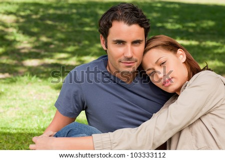 Man looking towards the sky with his friend who is resting her head on his shoulder as the sit on the grass - stock photo