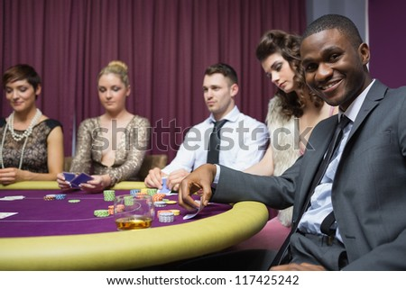 Man looking up from poker game and smiling in casino - stock photo