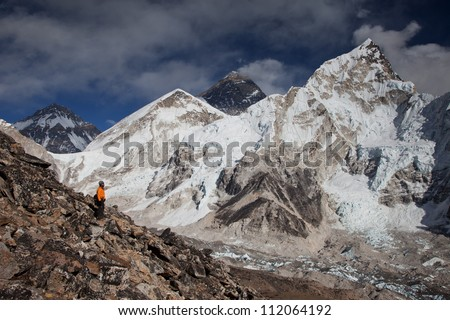 Man looking up to Himalayas and Mt Everest in Nepal while trekking. - stock photo