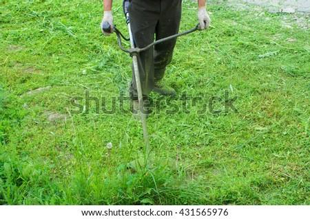 Man looks after a grass. Worker cuts off a grass a lawn-mower. - stock photo