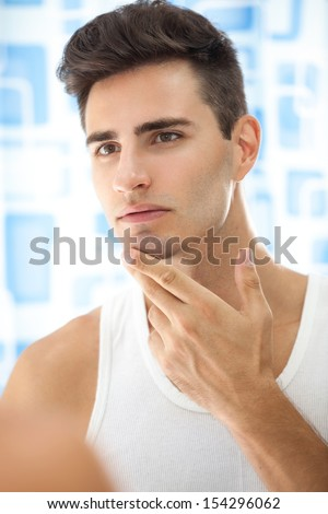 Man looks at his beard and thought about shaving - stock photo