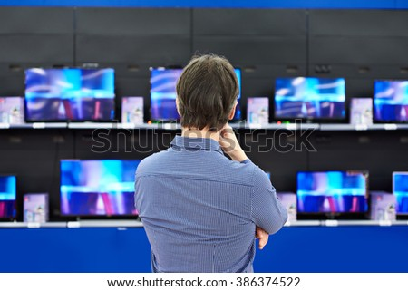 Man looks at LCD TVs in supermarket - stock photo